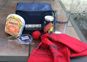 "Kit components on display: Lunchbox, compressed t-shirt ""sandwich"", bottle opener flash drive, coasters, challenge flag, energy drink, glass."